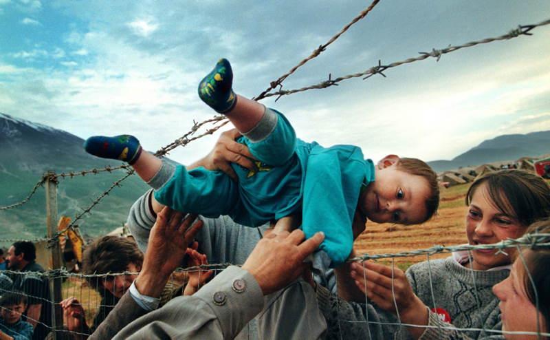 Dvojročný utečenec z Kosova, Agim Shala, je podávaný cez ostnatý plot do rúk prarodičov v tábore utečencov v Kukes v Albánsku.