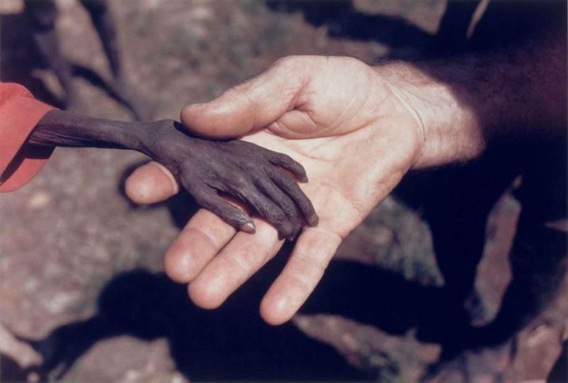 Misionár drží za ruku hladujúceho chlapca v Ugande. Rok 1980.