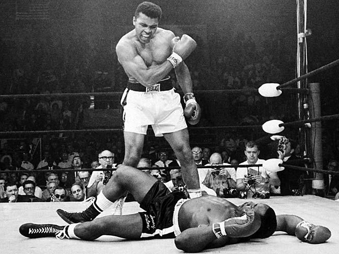 """Odveta zápasu medzi Muhammadom Alim a Sonnym Listonon bola dosť kontroverzná, pretože Liston padol hneď v prvom kole. Táto fotka Aliho, kde stál nad svojou korisťou sa stala najikonickejšou fotografiou muža, ktorý bol známy ako """"Najväčší""""."""