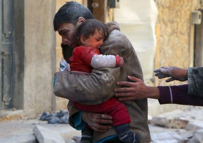 Chlapec zachraňuje svoju sestru z pod trosiek ich dobu v Sýrii.
