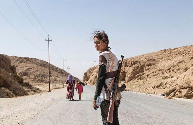 Yezidské dievča nesie pušku aby ochránilo svoju rodinu pred ISIS.