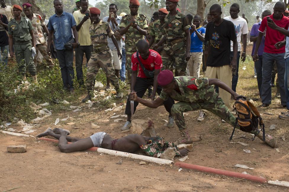 Vojak Africkej armády bodá mŕtvolu muža, ktorý bol zabitý kvôli obvineniu, že sa spriahol so seléckymi bolovníkmi. Bangui 5.2.2014.