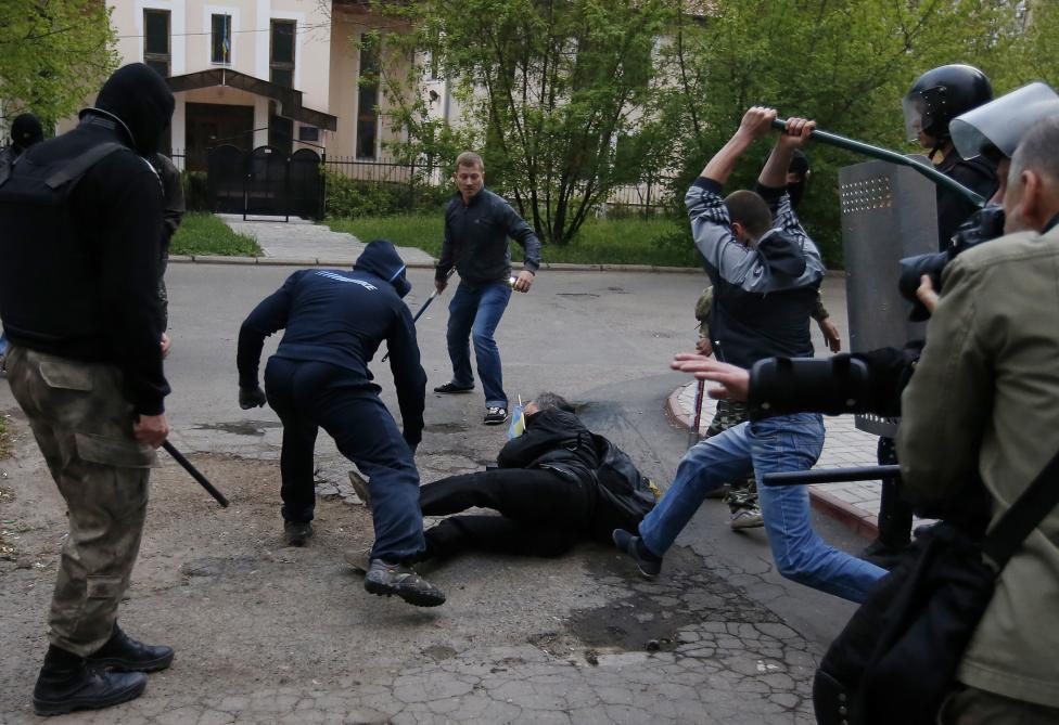 Pro-ruský demonštranti útočia na pro-ukrajinského demonštranta počas demonštrácii v Donecku. 28.4.2014.