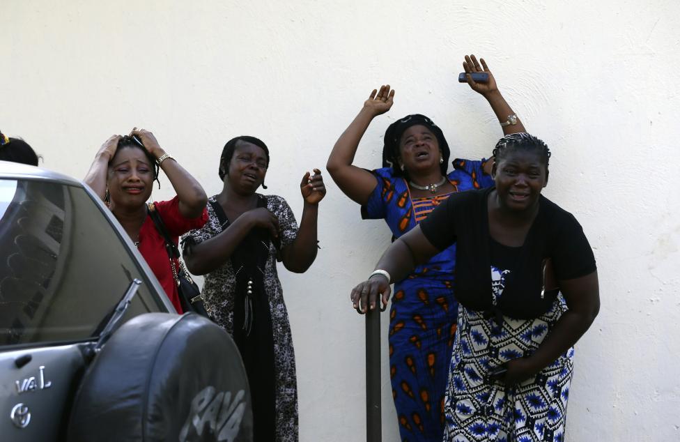 Okoloidúci reagujú na obete výbuchu bomby, ktoré akurát prinášajú do nemocnice. Nigéria, 14.4.2014.