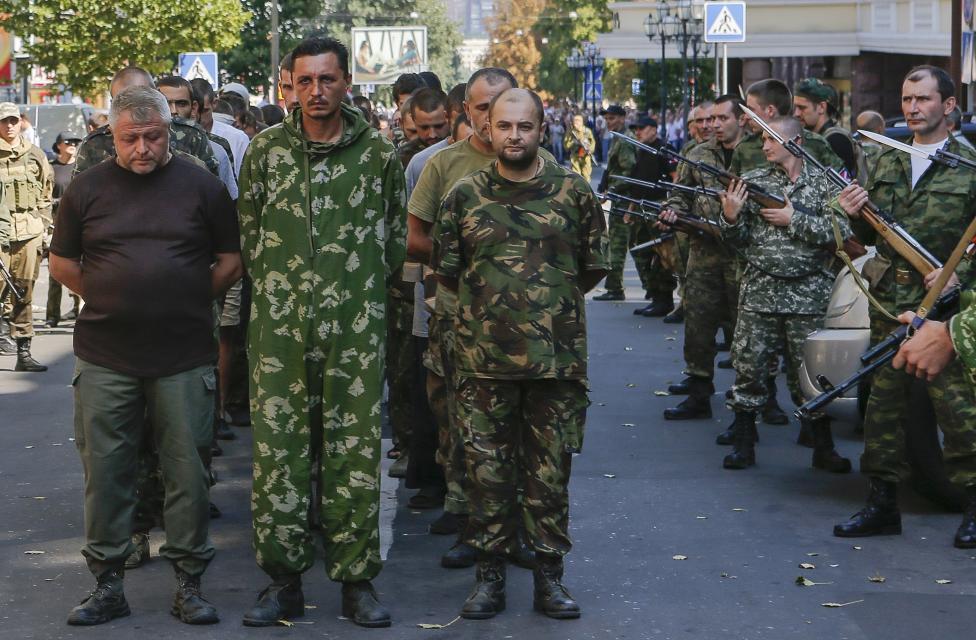 Ozbrojení ruskí separatisti sprevádzajú ukrajinských vojnových zajatcov v Donecku. 24.8.2014.