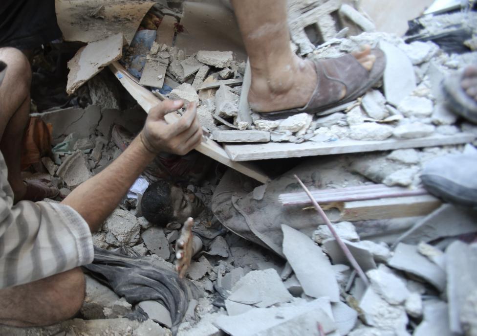 Palestínčania zachraňujú Mahmúda al-Ghola, ktorý bol uväznený pod troskami domu v meste Rafah. 3.8.2014.