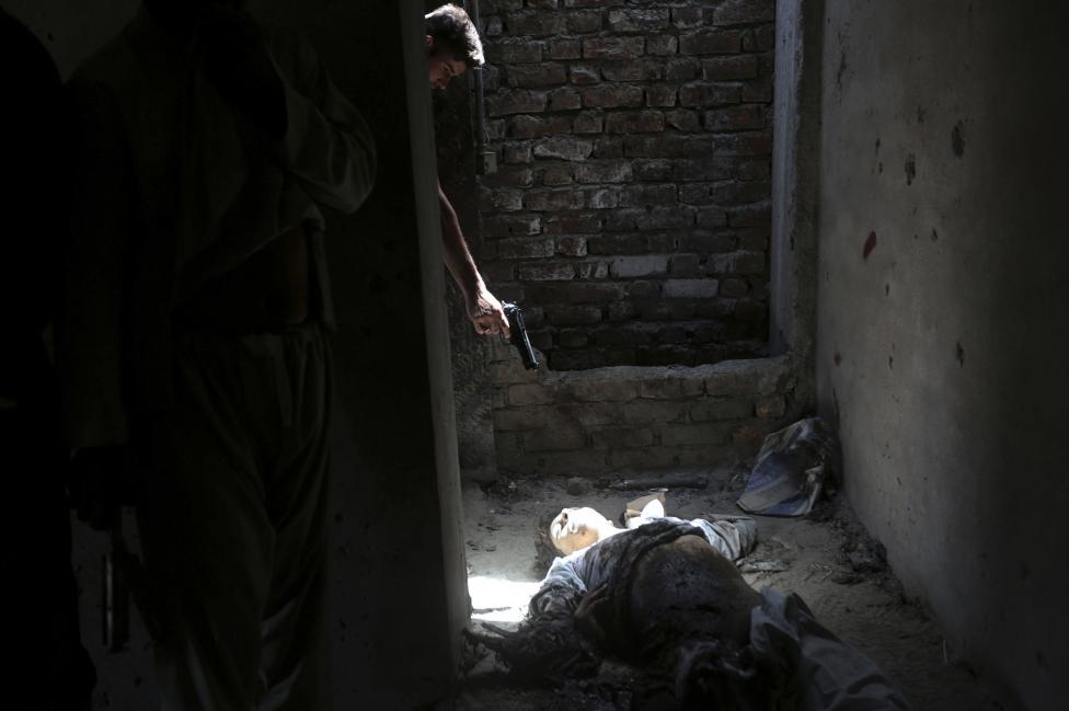 Afgánsky vojak mieri zbraňou na mŕtve neznáme telo a ukazuje tak nenávisť k povstalcom po útoku na letisko v Kábule. 17.7.2014.