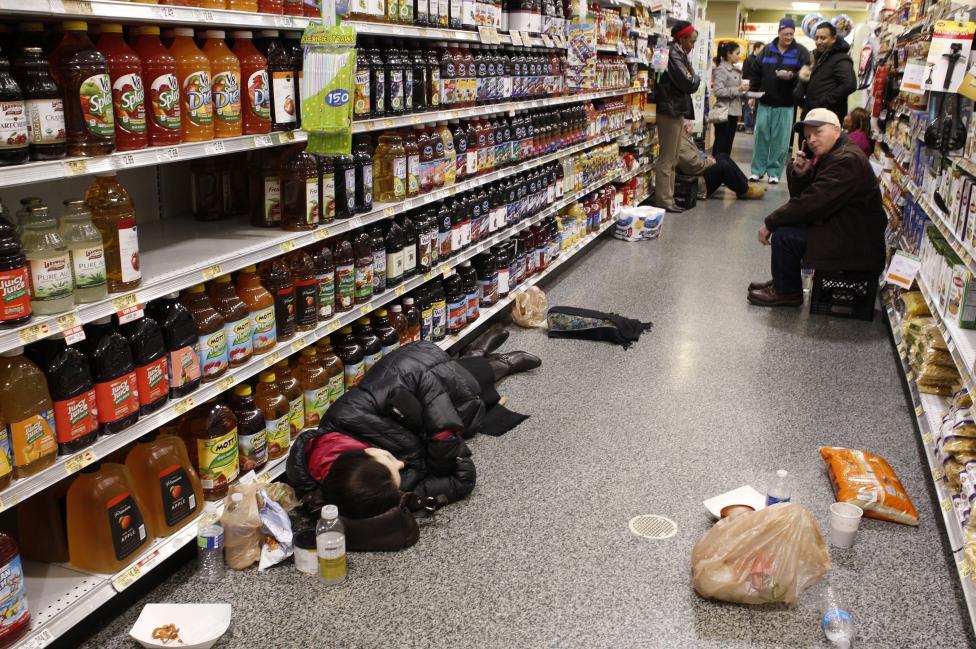 Ľudia oddychujú v uličke v obchode s potravinami po snehovej búrke v Atlante. Georgia, 29.1.2014.