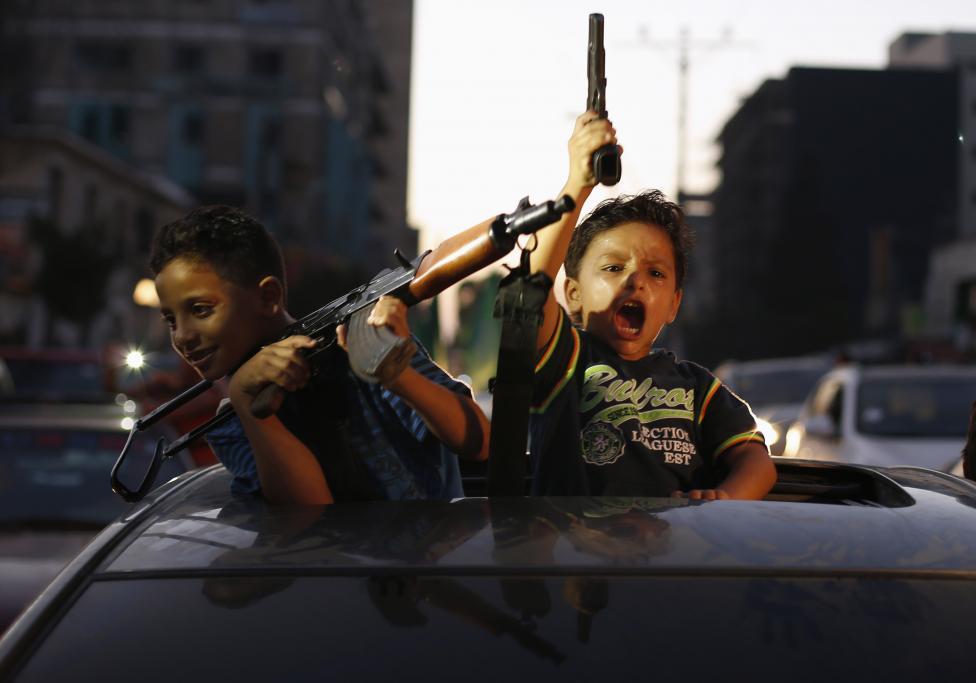 Palestínske deti držia zbrane a oslavujú, po tom, čo im povedali, že vyhrali nad Izraelom. NAsledovalo zastavenie paľby v Gaze. 26.8.2014.