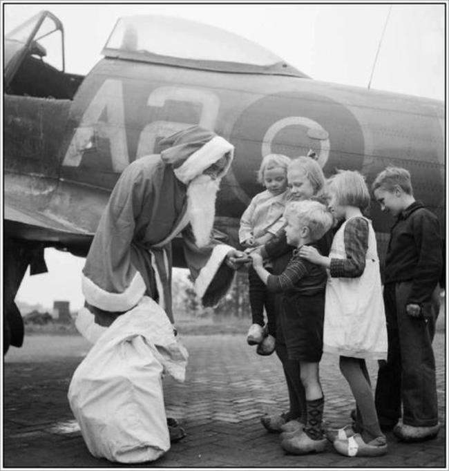 Britský pilot rozdáva holandským deťom potraviny. Nemecko prestalo zásobovať Holandsko jedlom, palivom. (13. december 1944)
