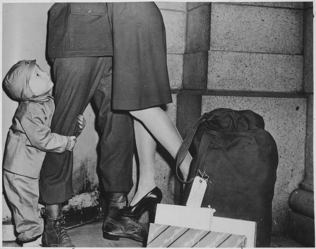 Malý chlapec zviera svojho otca, vojaka, ktorý prišiel na Vianoce domov (1944).
