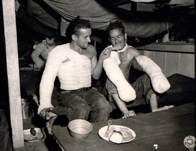 Sgt Edward Good pomáho svojmu kamarátovi pri vianočnej večeri v poľnej nemocnici v Belgicku (1944).