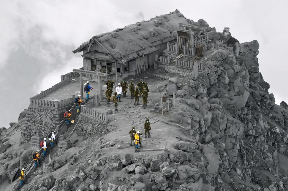 Záchranári vstupujú do popolom pokrytej svätyne v blízkosti vrcholu Mt. Ontake v Japonsku, ktorá vybuchla a zabila 56 ľudí.