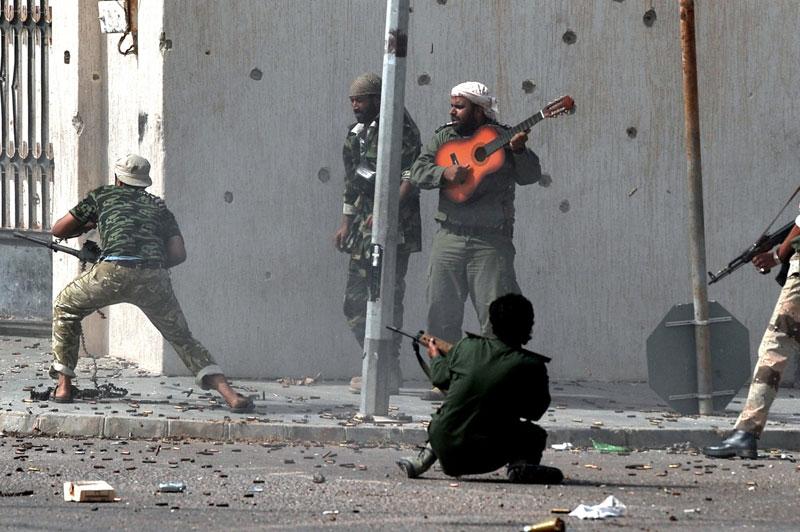 Na prvej fotografii Arisa Messinisa vidíme scénu z lýbijskej občianskej vojny z roku 2011. Práve prebiehala prestrelka medzi stúpencami Kaddáfího a rebelmi, ale ani to nezabránilo neznámemu mužovi, aby len tak na ulici hral na svojej gitare. Ako sám Aris povedal, neznámy gitarista sa snažil povzbudiť ostatných bojovníkov, ale priamo boja sa sám nezúčastnil, zostal verný svojej hudbe.