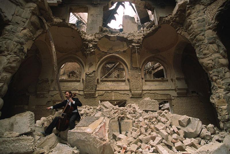 Na fotografii od Mikhaila Evstafieva vidíme hudobníka Vedrana Smailoviča, ktorý je známy ako Čelista zo Sarajeva. Fotka vznikla v roku 1992 počas vojny, ktorá prebiehala v Bosne. Vedran hrával často zadarmo na pohreboch, kde sa pochovávali obete vojny a na zábere nižšie ho vidíme hrať v zničenej Národnej knižnici. Tá bola zdevastovaná po jednom zo srbských útokov a zničené tak bolo obrovské množstvo vzácnej literatúry.