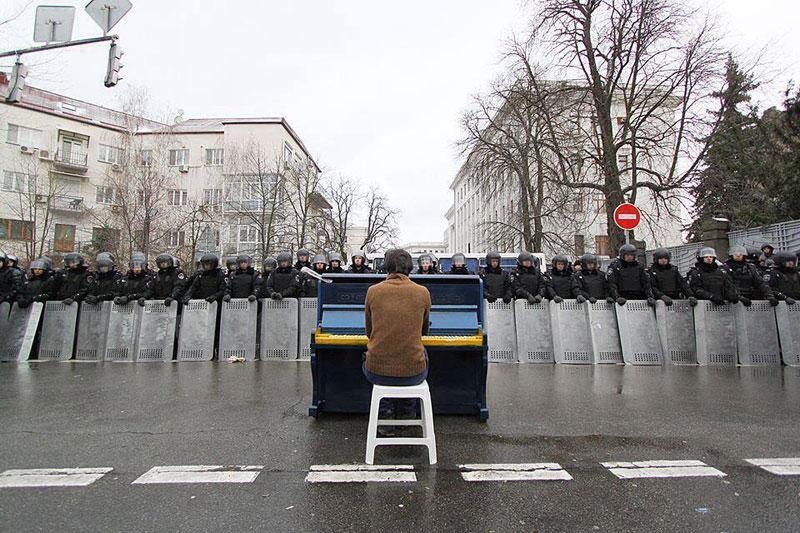 Táto fotka pochádza z hlavného mesta Ukrajiny. Státisíce ľudí protestovali a bojovali za odstúpenie prezidenta Yanukovicha. Na fotke od Andrewa Meakovskiho vidíme Markiyana Matsekha, ktorý hrá na klavíri pred bariérou policajných tiel, ktoré chránia prezidentský úrad. Jeden z organizátorov protestov povedal, že Matsekh hral napríklad Chopina alebo legendárne We are the Champions od Queen.
