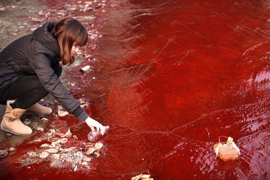 Novinárka berie vzorku znečistenej vody z rieky Jianhe.