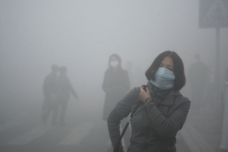 Mladá žena v meste Peking, kde je miera smogu až 40-krát výššia, ako je medzinárodný štandard.