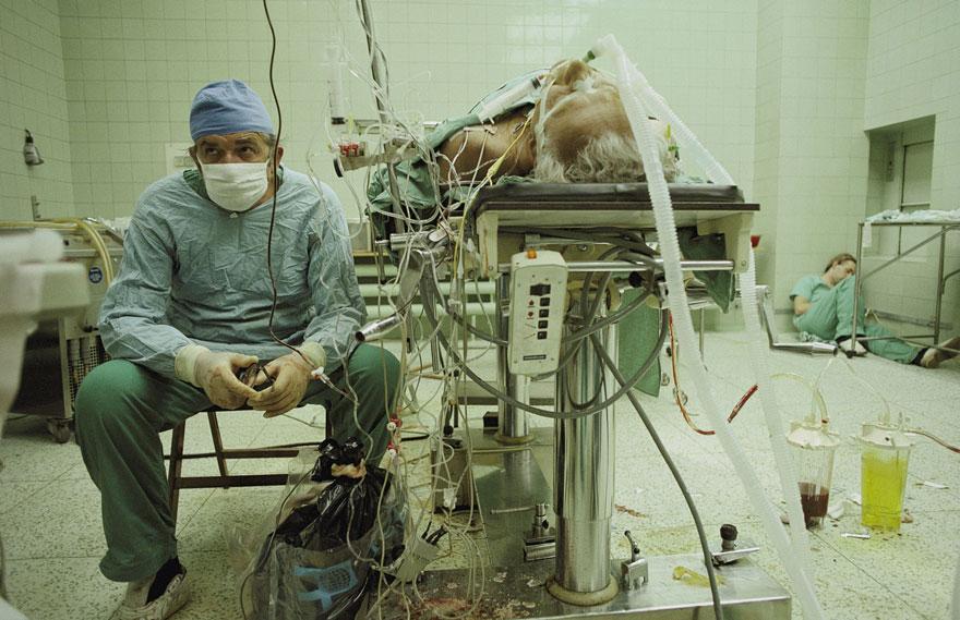 Srdcový chirurg sedí úplne vyčerpaný po 23-hodinovej transplantácii srdca. Jeho asistent spí v rohu.