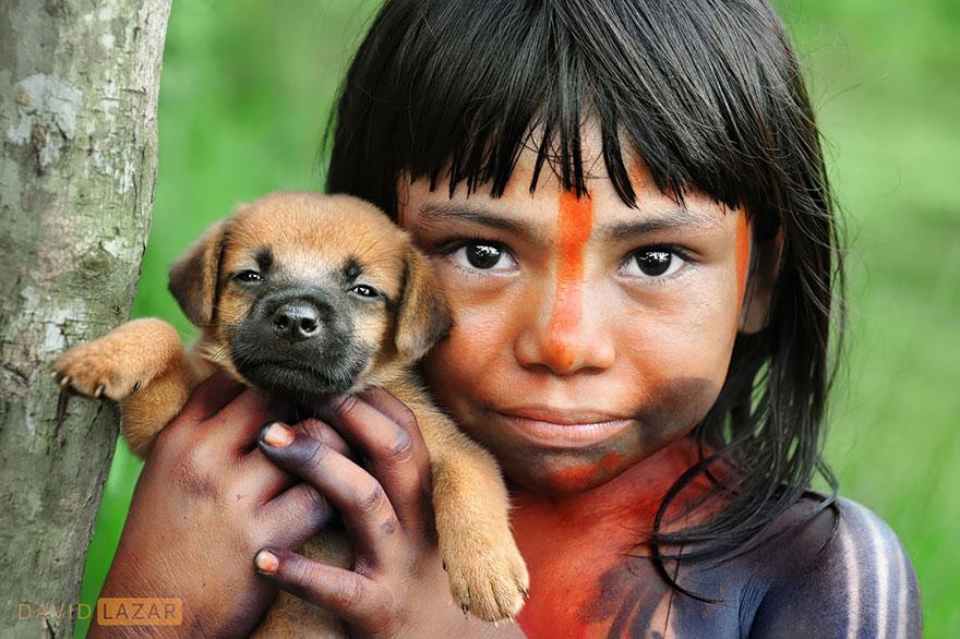 Tradične pomaľované dievčatko si stráži svojho psíka.