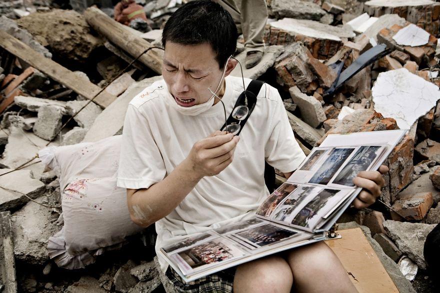 Muž plače popri tom, ako listuje v rodinnom albume, ktorý našiel v troskách svojho niekdajšieho domu.