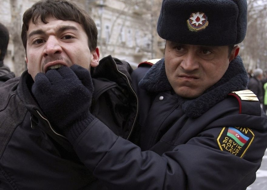 Protestant hryzie policajta, ktorý sa ho snaží spacifikovať.