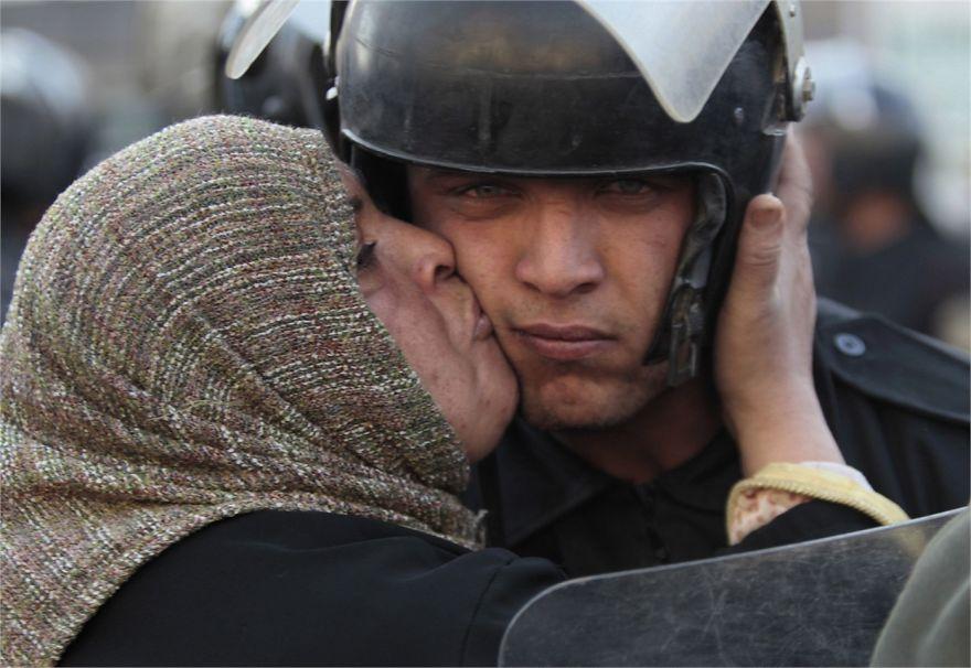 Egyptská žena bozkáva policajta, ktorý odmietol zaútočiť ohňom na protestantov.